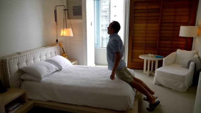 video of man jumping on the bed in slow motion - ora di andare a letto video stock e b–roll