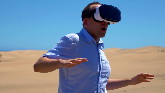 video von mann mit virtual-reality-brille auf der sahara - um geld spielen stock-videos und b-roll-filmmaterial