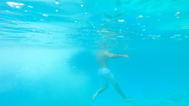 vidéos et rushes de vidéo 4k d'hommes qui sautent dans la mer et nagent sous l'eau tout en profitant des vacances d'été à zakynthos en grèce - station de vacances