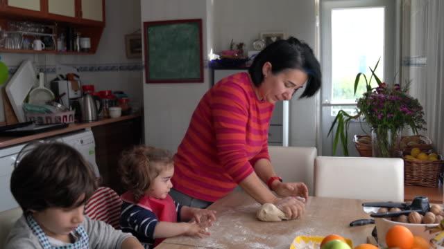 vidéos et rushes de vidéo 4k de la mère et des enfants cuisiner pizza dans la cuisine - moyen orient