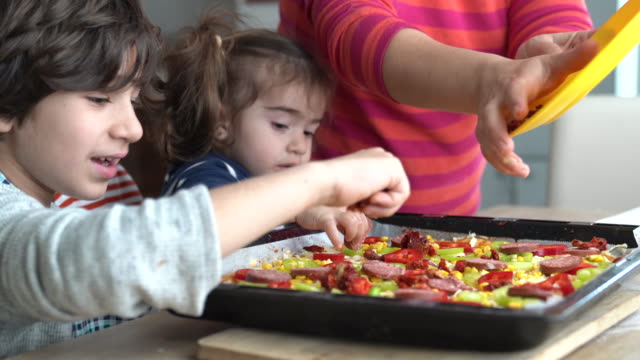 4k video of mother and children cooking pizza in kitchen - selimaksan stock videos & royalty-free footage