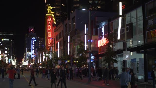 video of people partying and busy traffic at night, granville street, vancouver, british columbia, canada, north america - västerländsk text bildbanksvideor och videomaterial från bakom kulisserna