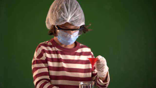 hd video av porträtt av skolpojke gör kemi experiment med färg vätskor - selimaksan bildbanksvideor och videomaterial från bakom kulisserna