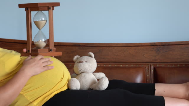 UHD vidéo de femme enceinte, compter le temps avec sablier