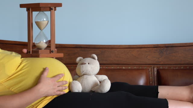 UHD Video Of Pregnant Woman Counting Time With Hourglass