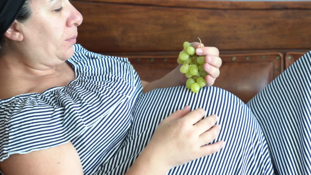 UHD vidéo de femme enceinte couchée sur le canapé