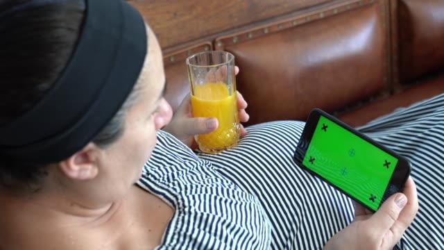 UHD vidéo d'une femme enceinte à l'aide de téléphone Mobile avec écran vert
