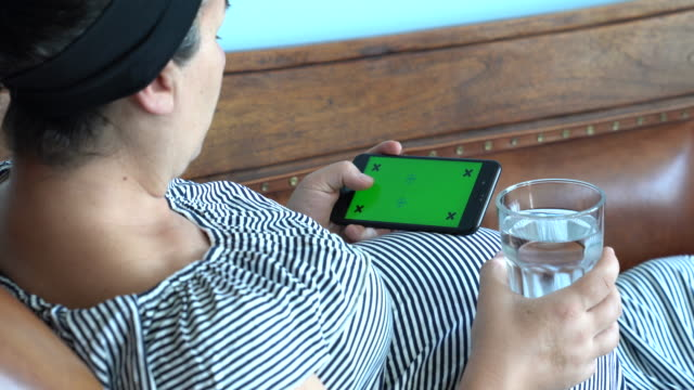 UHD Video van zwangere vrouw met behulp van mobiele telefoon met groen scherm