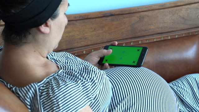 UHD Video Of Pregnant Woman Using Mobile Phone With Green Screen