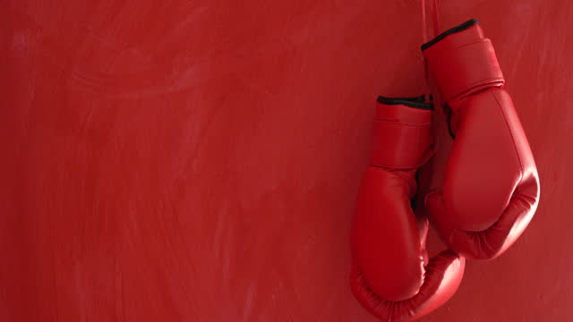 4k video of red boxing gloves hanged on red wall - boxing glove stock videos & royalty-free footage