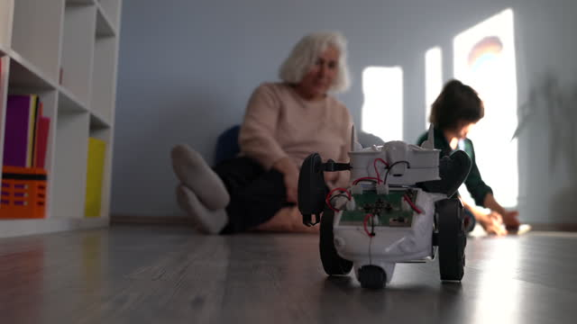 video of schoolboy playing with toy robot in living room while grandmother is watching - selimaksan stock videos & royalty-free footage