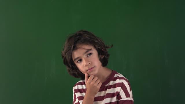 vidéos et rushes de vidéo 4k de la pensée d'écolier devant le clakboard - main au menton