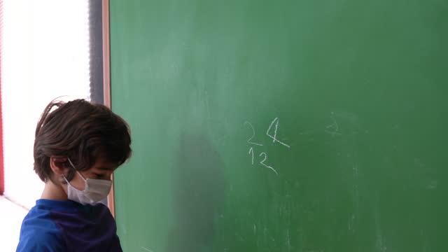 video of schoolboy wearing protective mask writing on blackboard - selimaksan stock videos & royalty-free footage