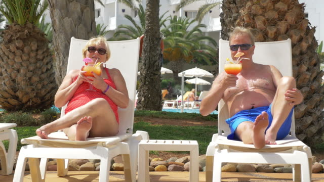 Video of senior couple drinking cocktails on sunbeds in 4K