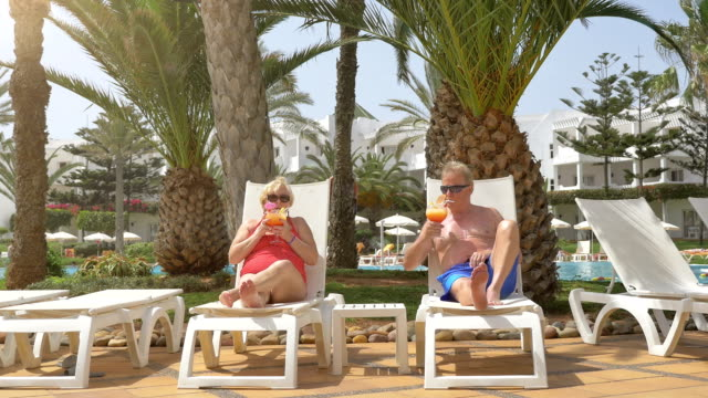 Video of senior couple drinking cocktails on vacations in 4K