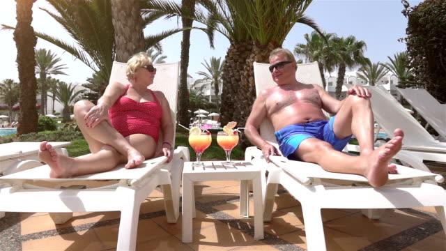Video of senior couple relaxing on the sunbeds-real slow motion