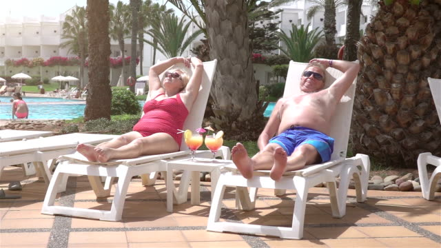 Video of senior couple sitting on the sunbeds-real slow motion