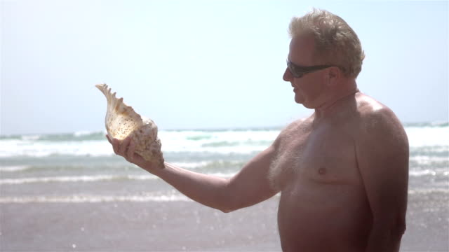 Video of senior man holding shell in real slow motion