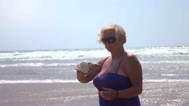 vídeos de stock, filmes e b-roll de vídeo do sênior mulher segurando o escudo real lenta - swimwear