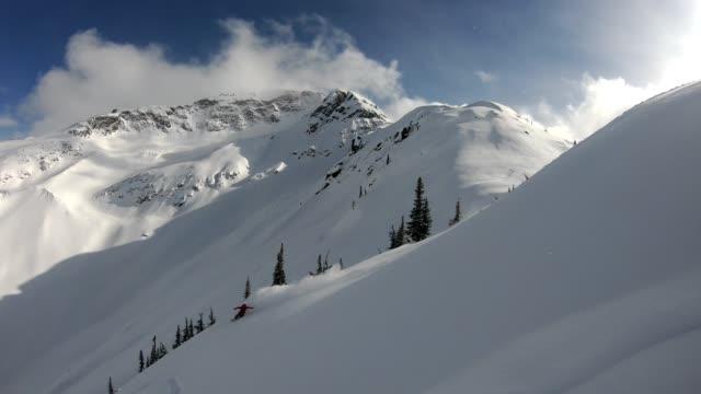 vídeos de stock, filmes e b-roll de vídeo do pó fresco da snowboarding nas montanhas - neve seca e solta