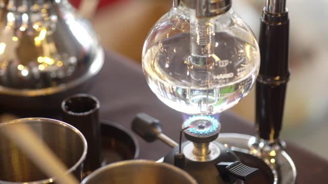 4k video von syphon kaffee auf gasherd. - ausgusstülle stock-videos und b-roll-filmmaterial