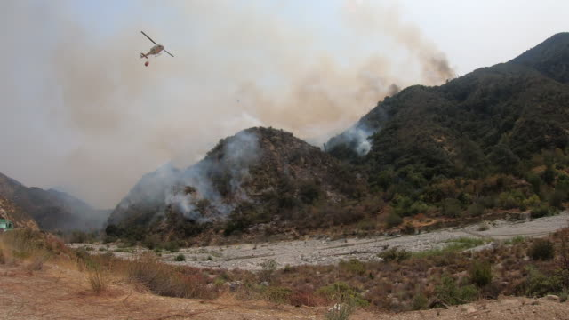4k video of the wildfire in california as a sky crane and bell helicopter drop water on fire - pine stock videos & royalty-free footage