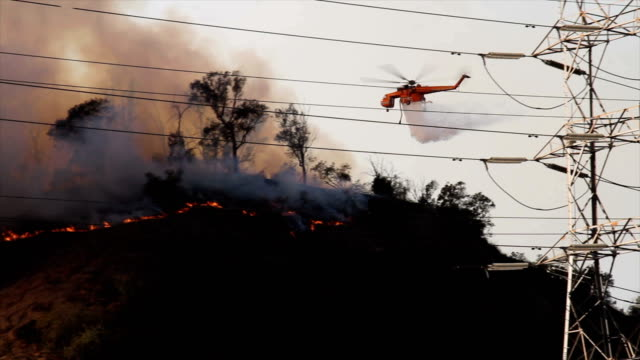 vídeos de stock e filmes b-roll de 4k video of the wildfire in california as a sky crane drops water on the fire - helicóptero