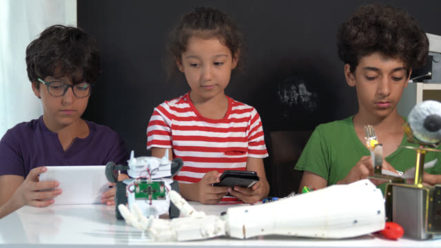 4k video of three school children trying to build a robotic arm - middle east stock videos & royalty-free footage