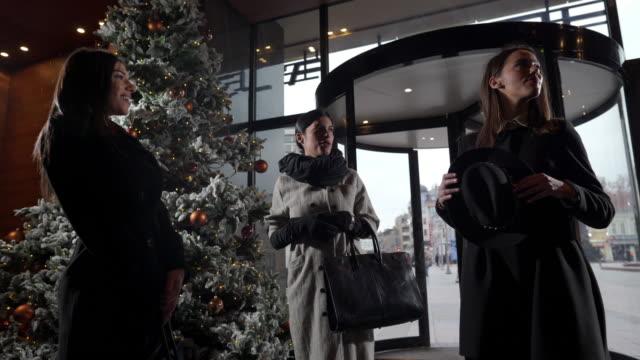 vídeos y material grabado en eventos de stock de vídeo de tres chicas adineradas esperando a sus amigos en el vestíbulo de un hotel - llegada