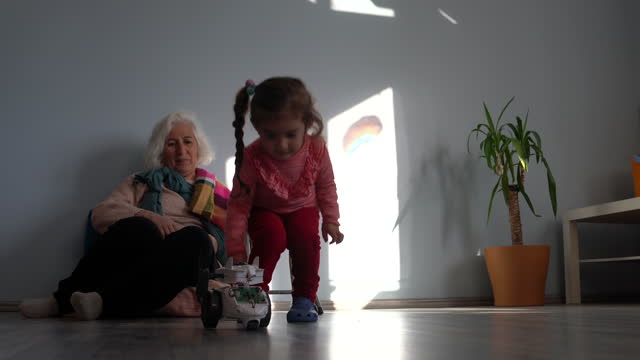video of toddler girl playing with toy robot in living room while grandmother is watching - selimaksan stock videos & royalty-free footage