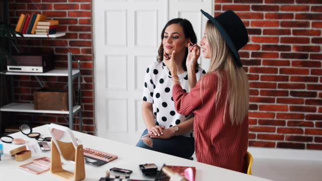 video of two cheerful young women sitting in a recording studio and one of them is applying make up on other while they are having fun filming a video tutorial for their internet and social media audience. - side hustle stock videos & royalty-free footage