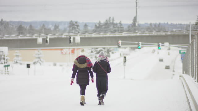 video of two young adults walking down a snow covered city street with winter clothes on. - fatcamera stock videos & royalty-free footage