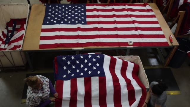 video of us flags being processed and folded at flagsource in batavia illinois june 27 2017 shots wide shot of large flag fabric being pulled through... - folded stock videos and b-roll footage