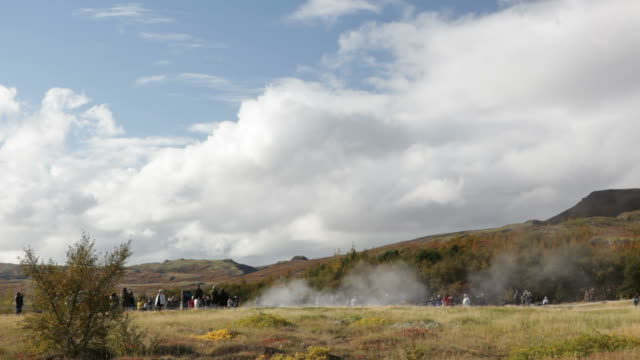 vídeos de stock, filmes e b-roll de hd vídeo de visitantes assistindo a islândia gêiser em erupção em geysir - gêiser strokkur