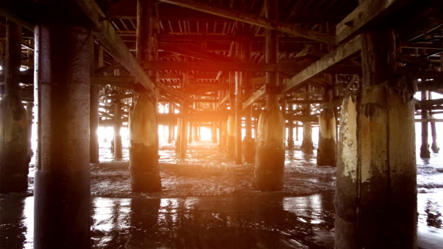 video of walking under pier in real slow motion - diminishing perspective stock videos and b-roll footage