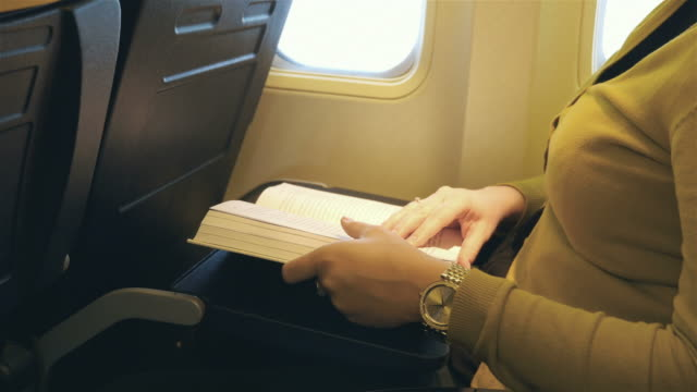 Video of woman reading a book in the airplane in 4K