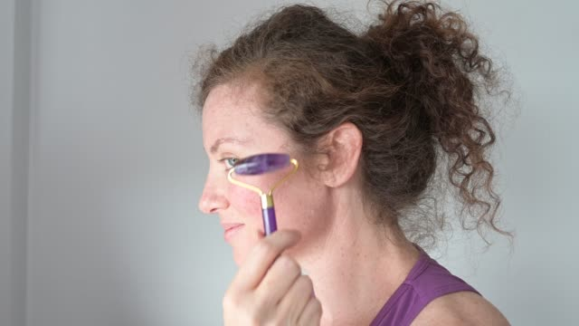 video of woman using amethyst crystal facial roller - new age stock videos & royalty-free footage