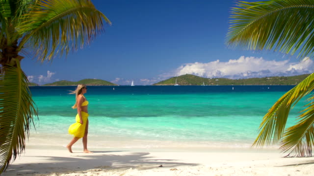 video of woman walking along the Caribbean beach shoreline