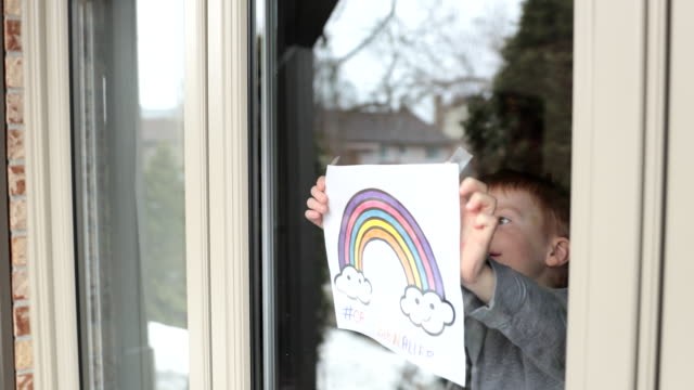 4k video of young boy sticking his drawing on home window during the covid-19 crisis - childhood stock videos & royalty-free footage