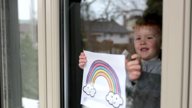 4k video von young boy klebt seine zeichnung auf home-fenster während der covid-19-krise - nachbar stock-videos und b-roll-filmmaterial