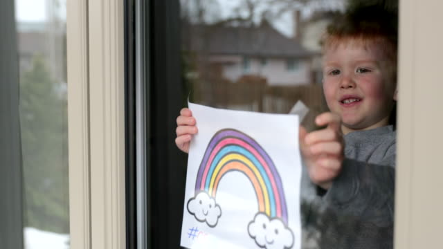 4k video of young boy sticking his drawing on home window during the covid-19 crisis - hope stock videos & royalty-free footage