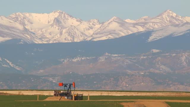 hd video oil derrick and snowy rocky mountains weld county colorado - oljepump bildbanksvideor och videomaterial från bakom kulisserna