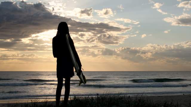 video portrait african-australian female surfer looking out at the surf at sunrise - surf stock videos & royalty-free footage