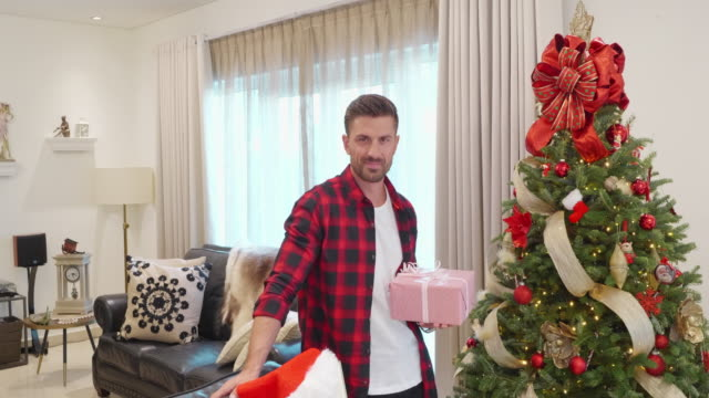 vídeos de stock e filmes b-roll de video portrait of a handsome man standing near christmas tree at home, holding christmas gift - camisa com botões