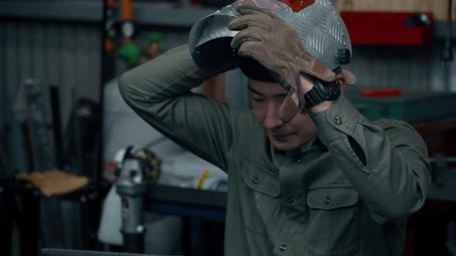 video portrait of a mid adult male putting on his welding helmet - welding helmet stock videos & royalty-free footage