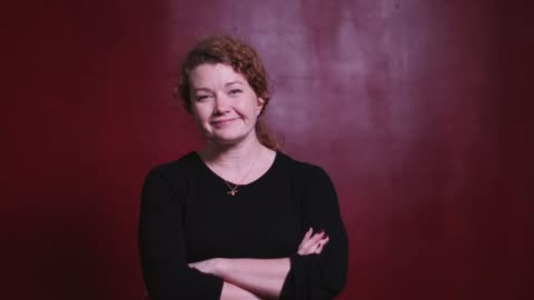 video portrait of a red haired caucasian woman against a red background - video portrait stock videos & royalty-free footage