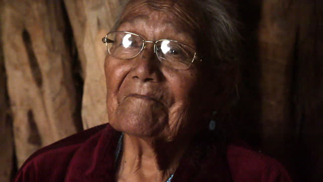 a video portrait of a smiling elderly navajo grandmother sitting in her authentic hogan in monument valley, arizona - indigenous north american culture stock videos & royalty-free footage