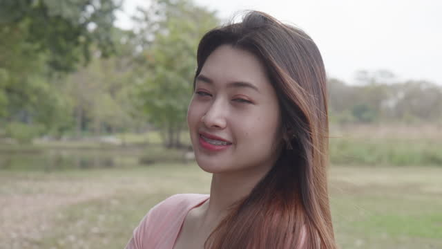 video portrait of a young woman standing in a park looking at the camera and smiling. - video portrait stock videos & royalty-free footage
