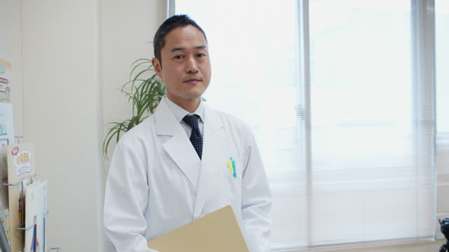 video portrait of handsome asian doctor - males stock videos & royalty-free footage