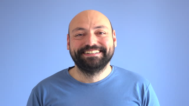 uhd video portrait of happy smiling adult man - studio shot stock videos & royalty-free footage